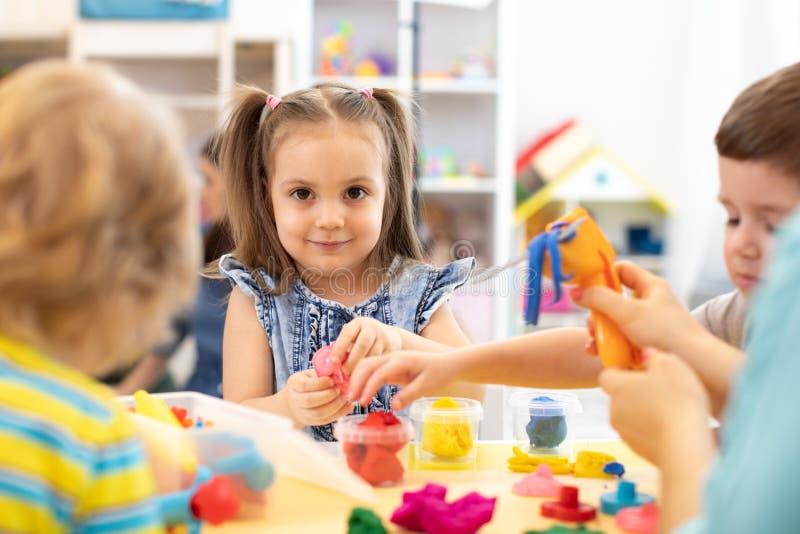 O grupo de crianças joga com argila de modelagem fotos de stock royalty free