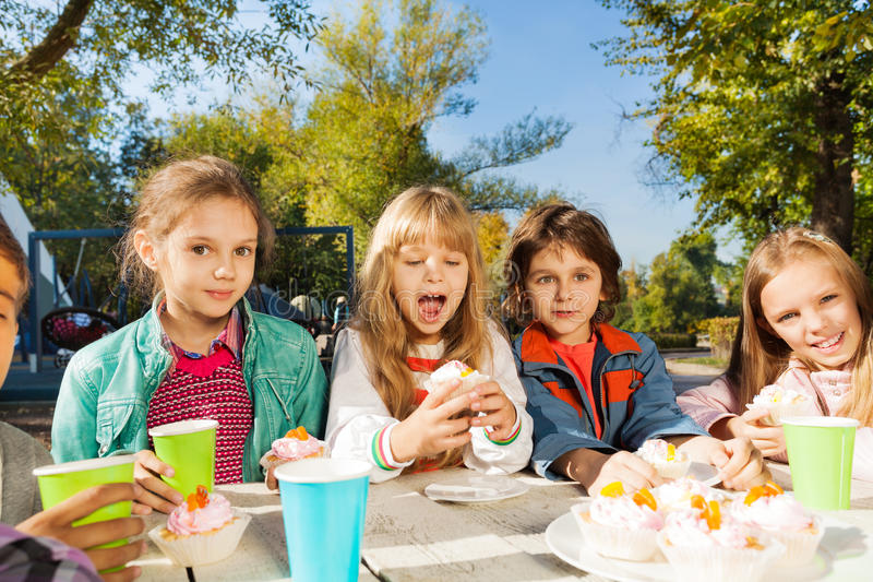 O grupo de crianças senta-se na tabela com copos coloridos fotos de stock
