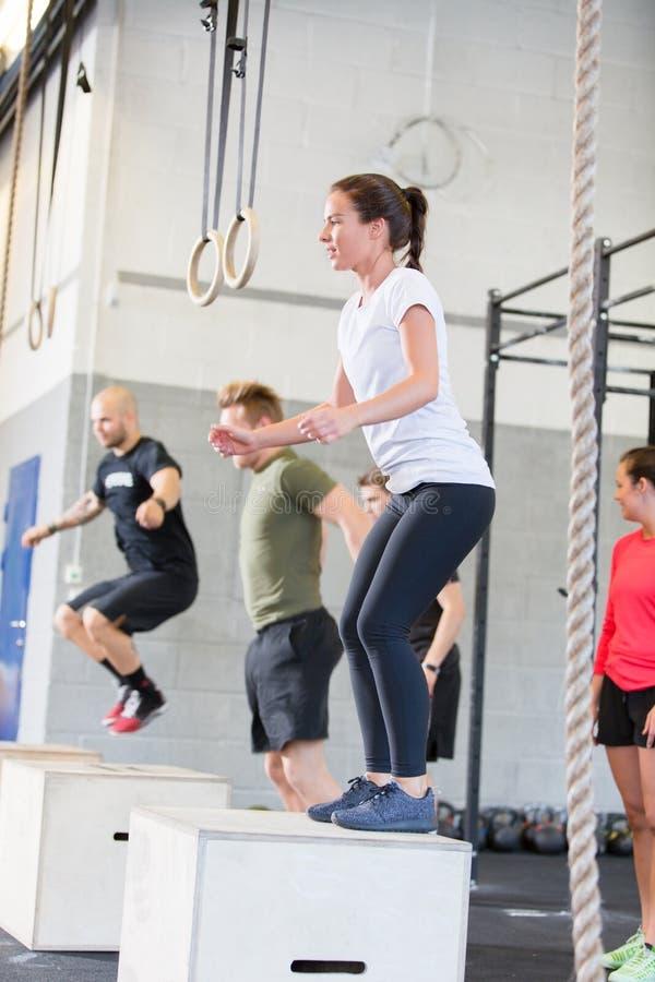 O grupo de Crossfit treina saltos da caixa fotos de stock