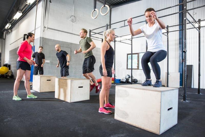 O grupo de Crossfit treina saltos da caixa foto de stock