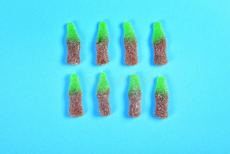 O grupo de doces da geleia transforma garrafas no fundo azul imagem de stock
