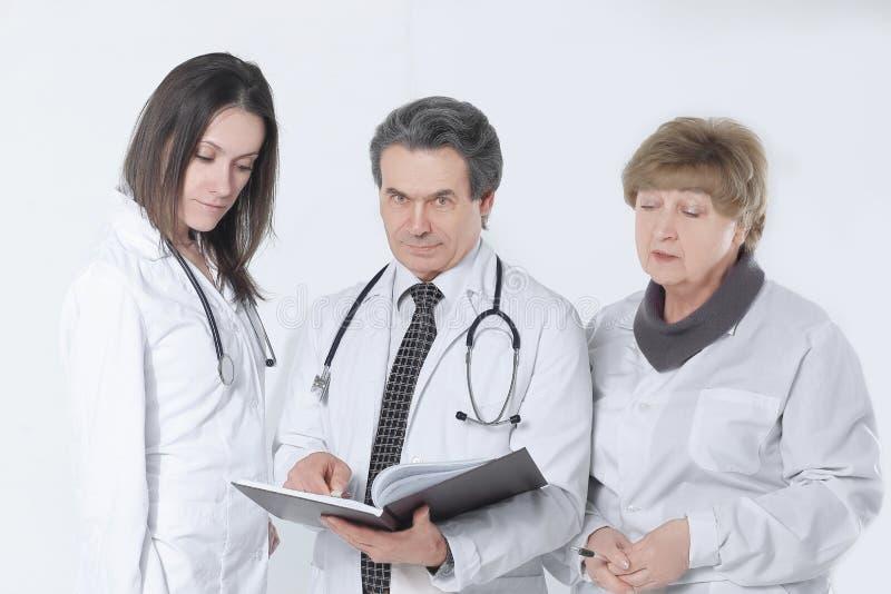 O grupo de doutores discute o diagnóstico do paciente O isolado imagens de stock royalty free