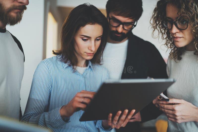 O grupo de empresários novos está procurando uma solução do negócio durante o tempo de funcionamento no escritório ensolarado fotografia de stock