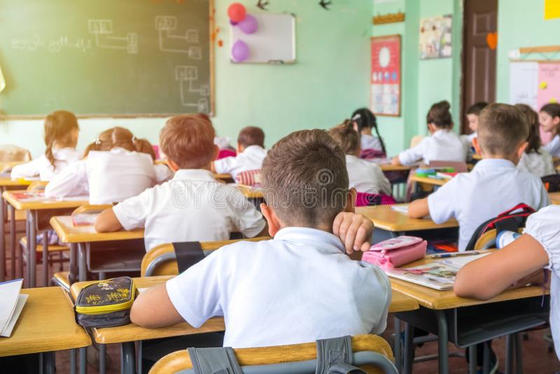 O grupo de escola caçoa o assento e a escuta o professor no classro foto de stock royalty free