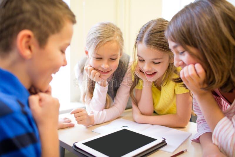 O grupo de escola caçoa com o PC da tabuleta na sala de aula imagens de stock