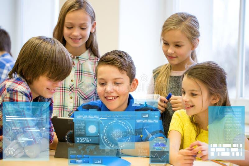 O grupo de escola caçoa com o PC da tabuleta na sala de aula fotografia de stock