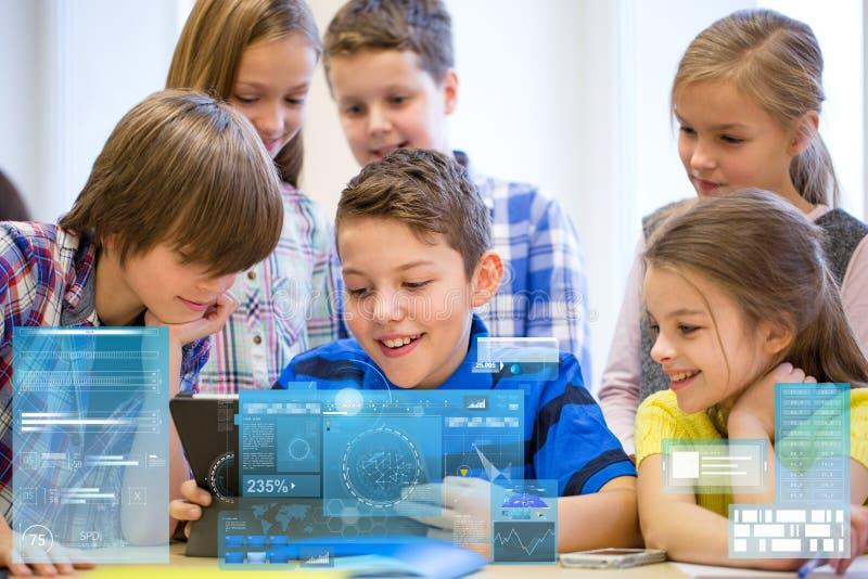O grupo de escola caçoa com o PC da tabuleta na sala de aula foto de stock
