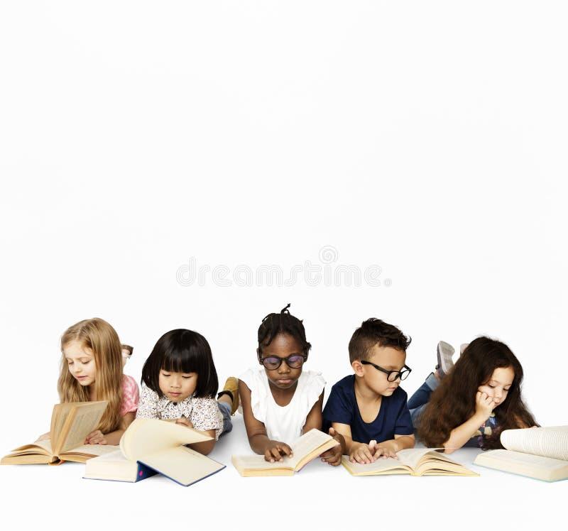 O grupo de escola caçoa a leitura para a educação foto de stock