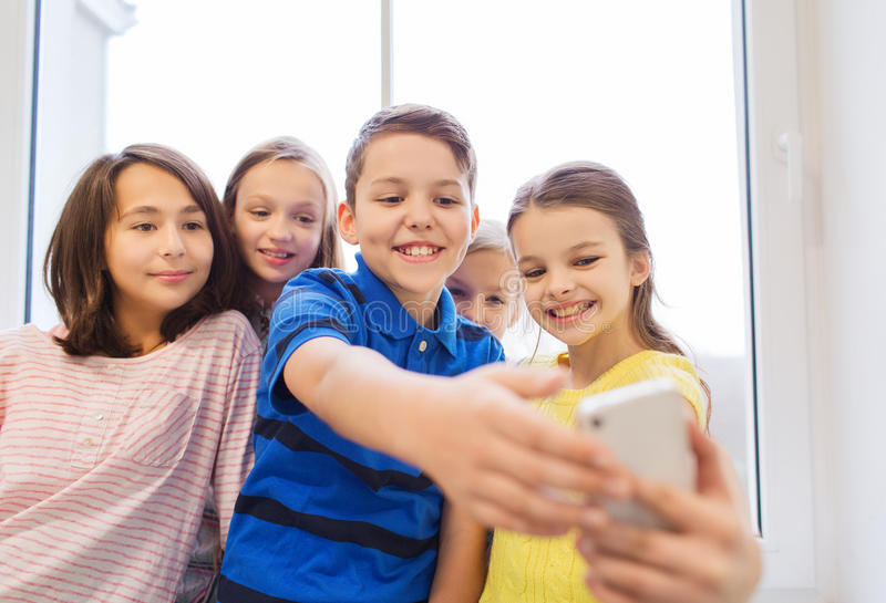 O grupo de escola caçoa a tomada do selfie com smartphone fotos de stock