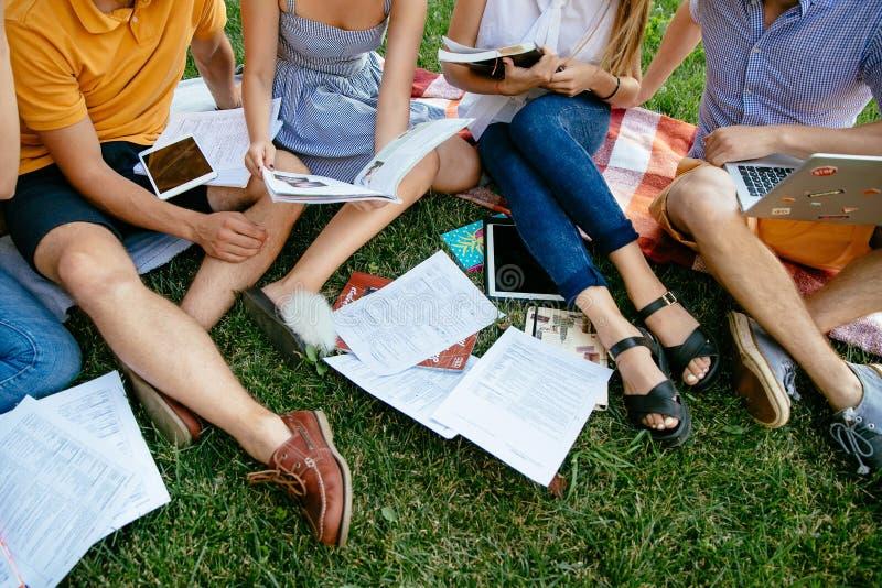 O grupo de estudantes com livros e a tabuleta estão estudando fora junto fotos de stock royalty free