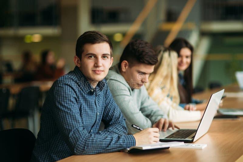 O grupo de estudantes universitário que estudam na biblioteca escolar, uma menina e um menino estão usando um portátil e estão co fotografia de stock royalty free