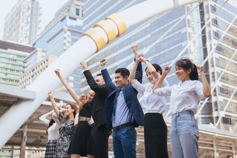 O grupo de executivos bem sucedido, mão da realização do sucesso da equipe aumentou foto de stock