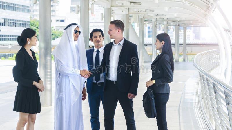 O grupo de executivos globais do homem e a mulher fala e agita han fotografia de stock royalty free