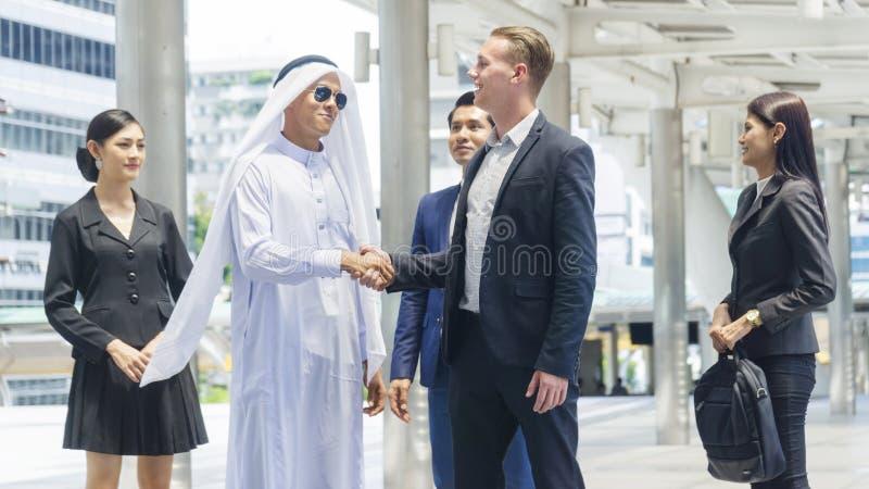 O grupo de executivos globais do homem e a mulher fala e agita han fotos de stock royalty free