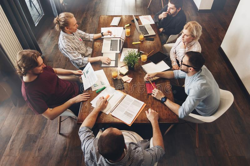 O grupo de gerentes criativos senta-se em torno da tabela Processo de trabalho T fotos de stock royalty free