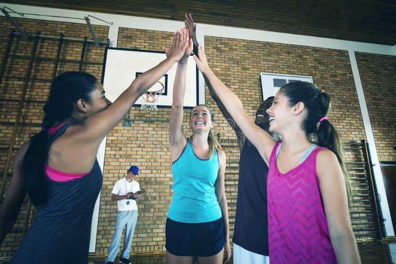 O grupo de High School caçoa a doação da elevação cinco no campo de básquete imagem de stock royalty free