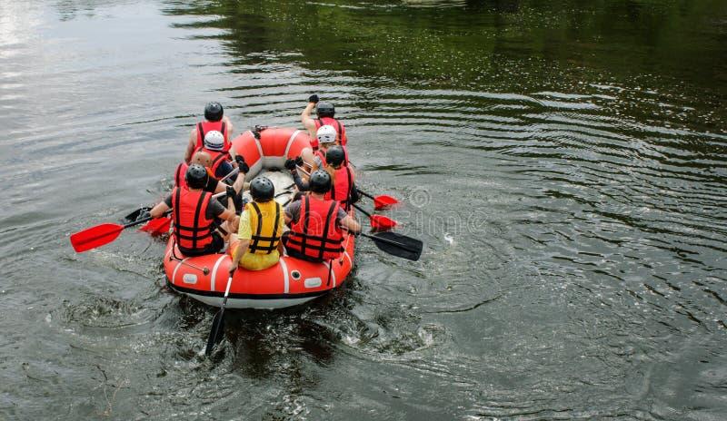 O grupo de homens e de mulheres, aprecia a água que transporta a atividade no rio imagens de stock