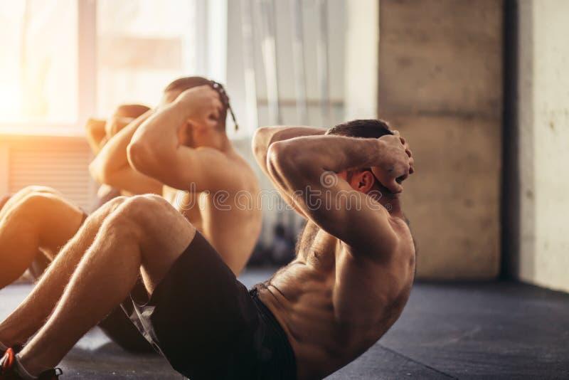 O grupo de homens e de mulheres que adultos atléticos executar se senta exercita acima imagens de stock royalty free