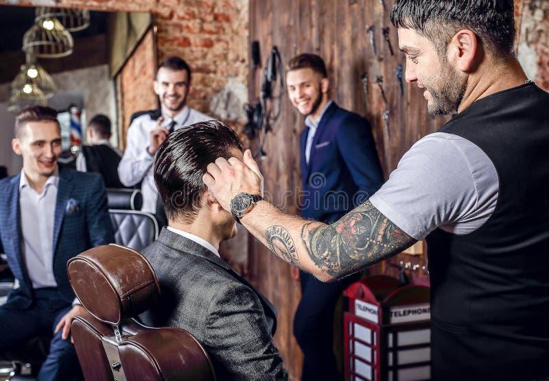 O grupo de homens positivos elegantes novos levanta no interior do barbeiro fotos de stock royalty free