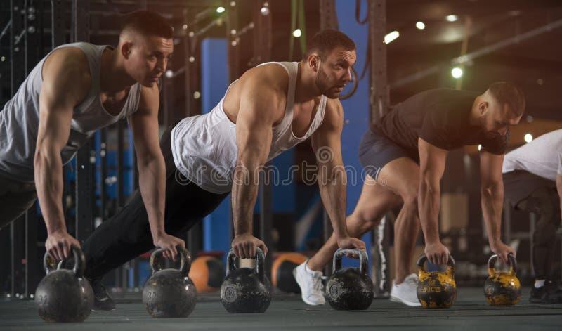 O grupo de homens que atl?ticos o treinamento empurra levanta no Gym fotos de stock royalty free
