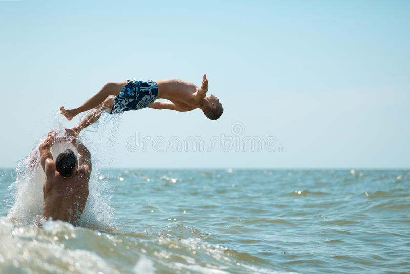 O grupo de indivíduos que estão no mar lanç acima do homem foto de stock royalty free