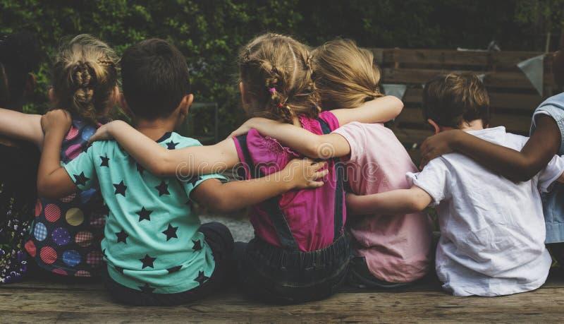 O grupo de jardim de infância caçoa amigos arma-se em torno do assento junto fotografia de stock