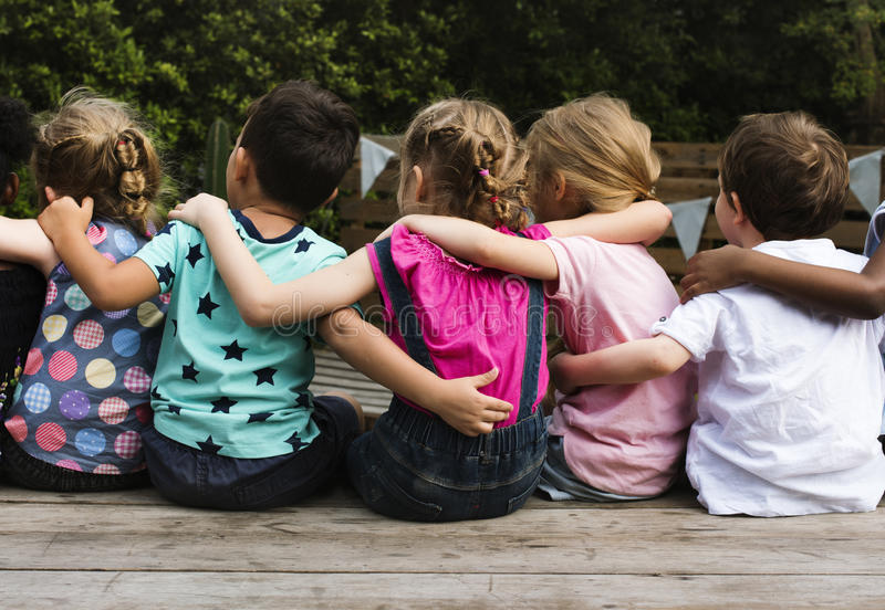 O grupo de jardim de infância caçoa amigos arma-se em torno do assento junto fotos de stock royalty free