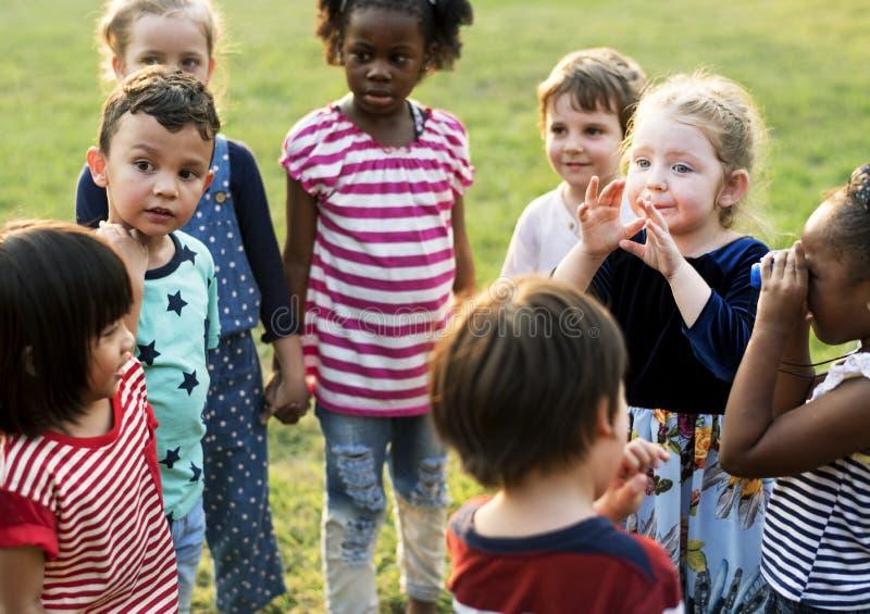 O grupo de jardim de infância caçoa os amigos que guardam as mãos que jogam no parque fotografia de stock royalty free