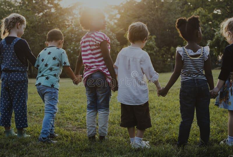 O grupo de jardim de infância caçoa os amigos que guardam as mãos que jogam no parque imagens de stock royalty free