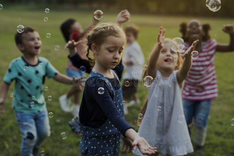 O grupo de jardim de infância caçoa os amigos que jogam o divertimento de sopro das bolhas foto de stock royalty free