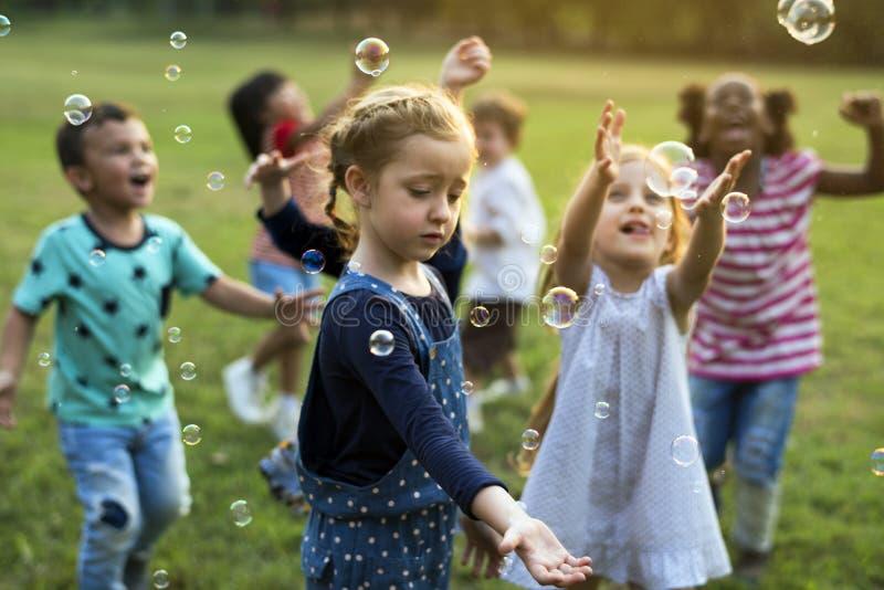 O grupo de jardim de infância caçoa os amigos que jogam o divertimento de sopro das bolhas fotos de stock royalty free