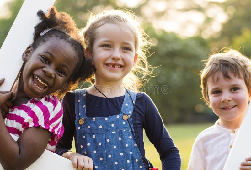 O grupo de jardim de infância caçoa os amigos que jogam o divertimento do campo de jogos e a manutenção programada fotografia de stock