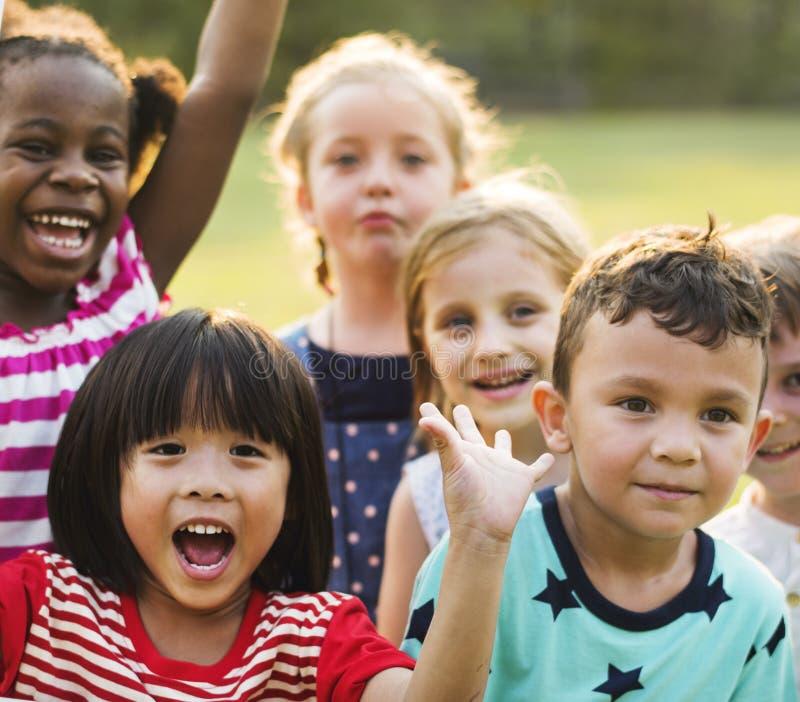 O grupo de jardim de infância caçoa os amigos que jogam o divertimento do campo de jogos e a manutenção programada fotos de stock