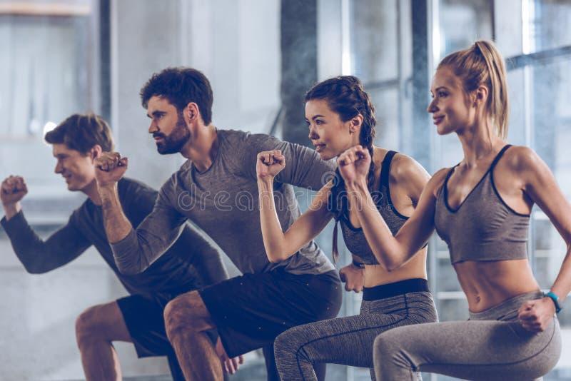 O grupo de jovens atléticos em fazer do sportswear investe contra o exercício no gym fotografia de stock