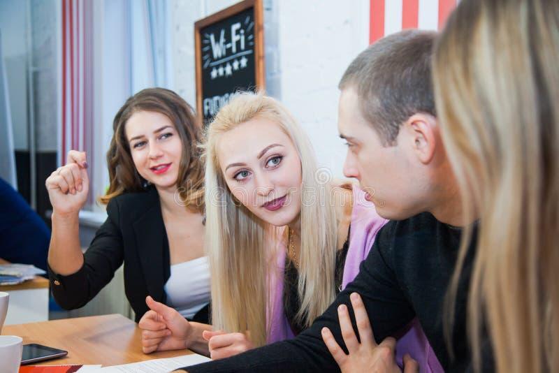 O grupo de jovens criativos senta e trabalha junto o original do sinal fotografia de stock