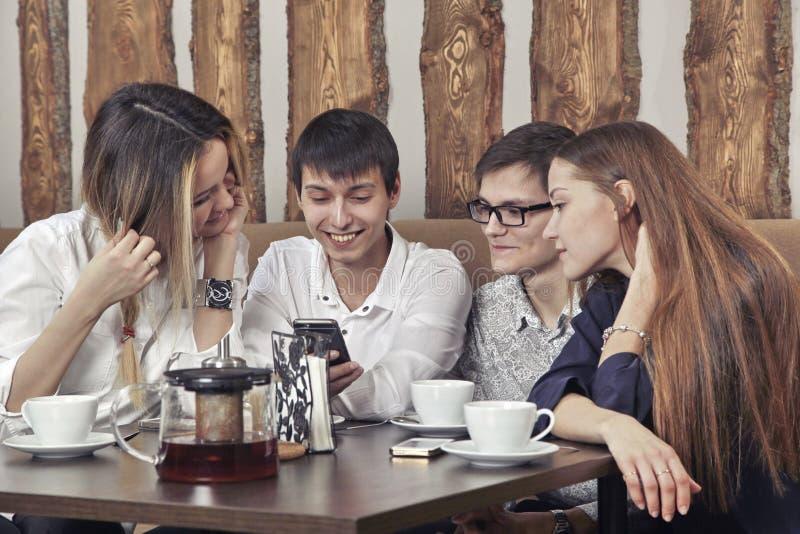 O grupo de jovens de dois pares de indivíduos e as meninas têm uma estadia do chá no café e a vista no smartphone absorbedly fotografia de stock