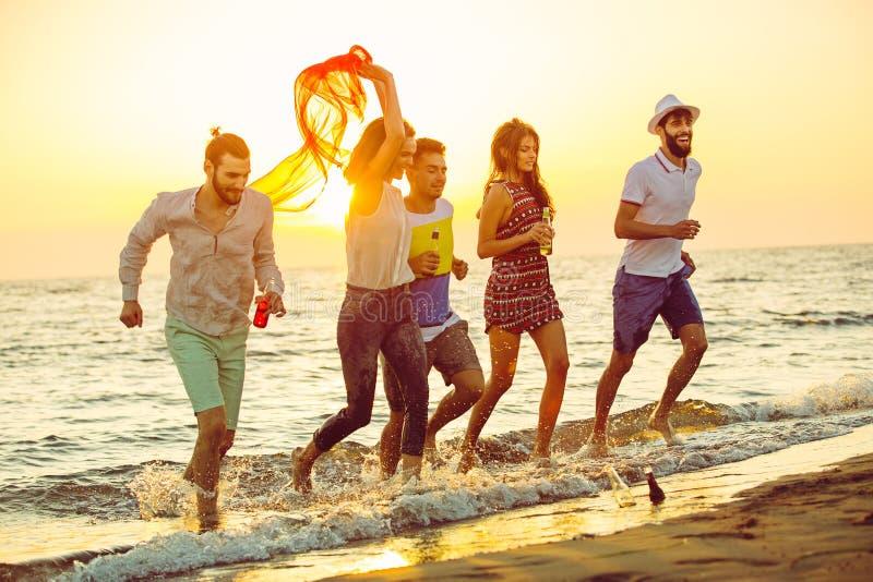 O grupo de jovens felizes está correndo no fundo da praia e do mar do por do sol foto de stock