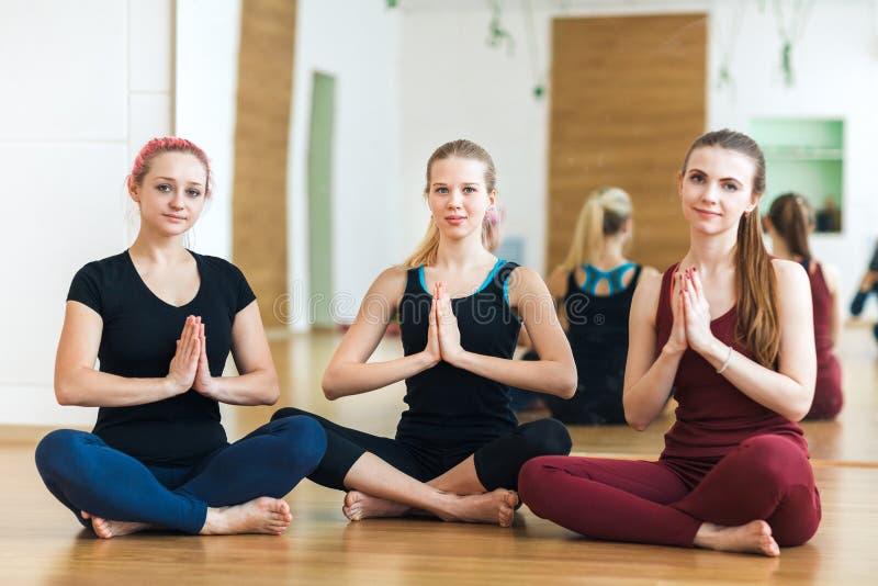 O grupo de jovens mulheres olha a câmera e o sorriso que meditam na pose dos lótus com mãos no namaste no gym yoga imagens de stock royalty free