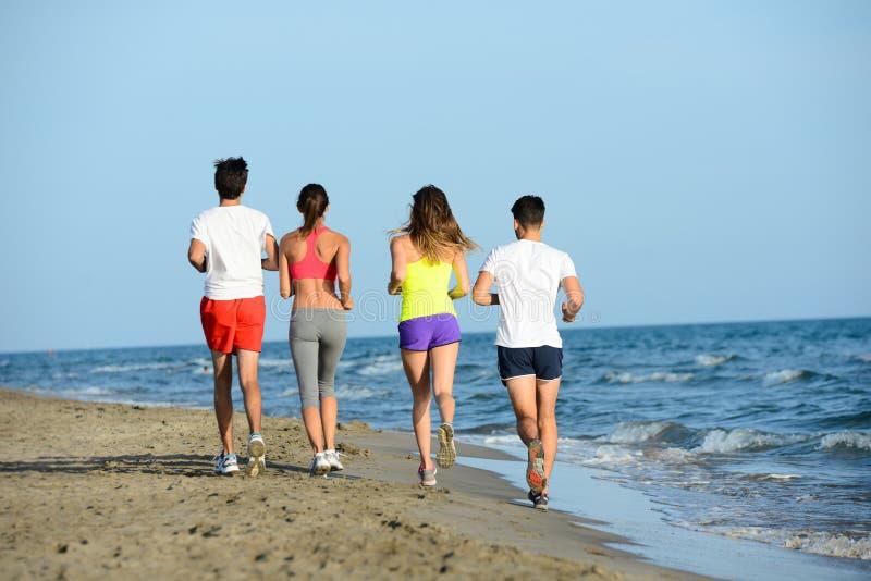 O grupo de jovens que correm na areia na costa de uma praia pelo mar no por do sol durante umas férias de verão ensolaradas vacat imagens de stock