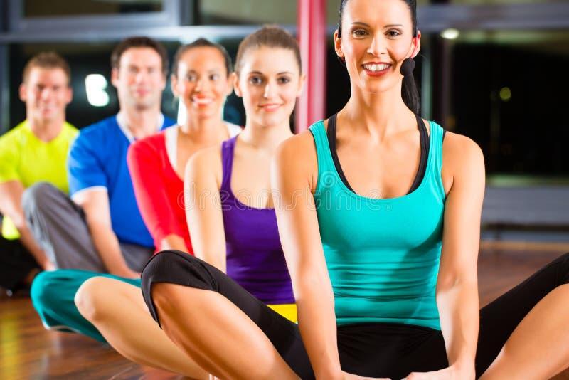 Grupo de pessoas e instrutor no esticão do gym imagem de stock royalty free