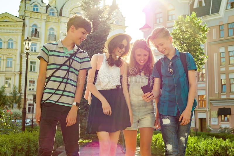 O grupo de juventude está tendo o divertimento, amigos felizes dos adolescentes que andam, falando apreciando o dia na cidade fotos de stock royalty free