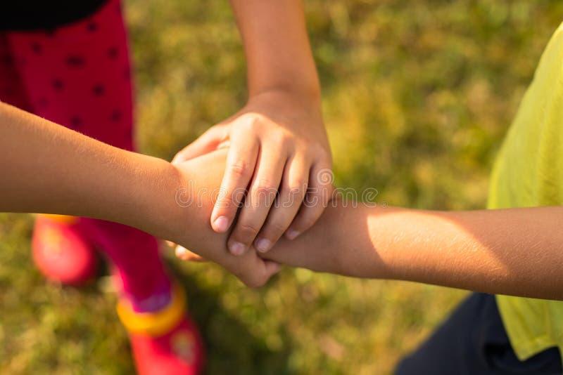 O grupo de mãos das crianças junta-se junto no jogo colaborador foto de stock