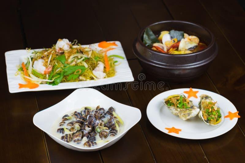 O grupo de marisco asiático com geoduck grelhado com cebola e graxa, escargot do coco, camarão fritou mexendo a aletria, moluscos fotografia de stock