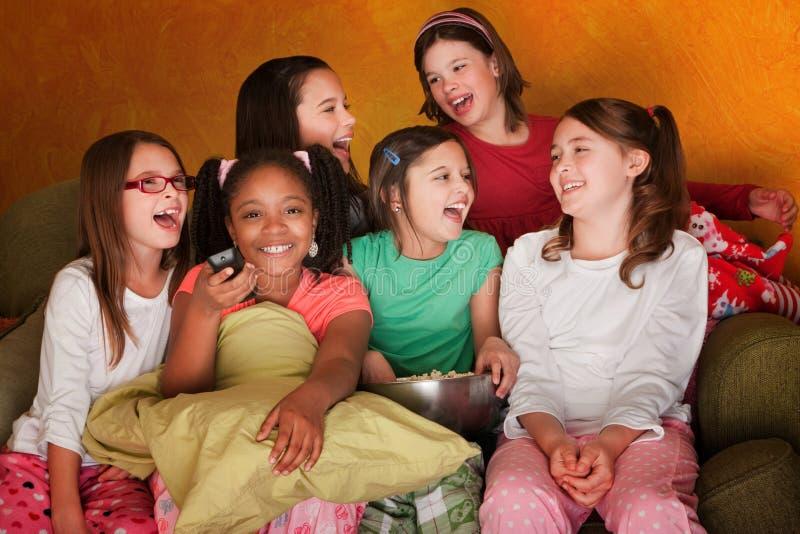 O grupo de meninas presta atenção à televisão imagens de stock royalty free
