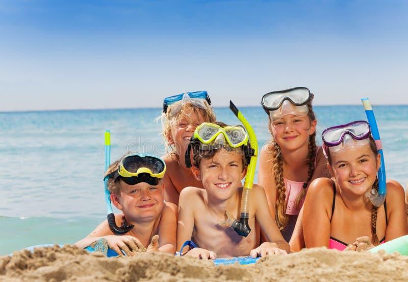 O grupo de meninos e o la das meninas no mar encalham foto de stock