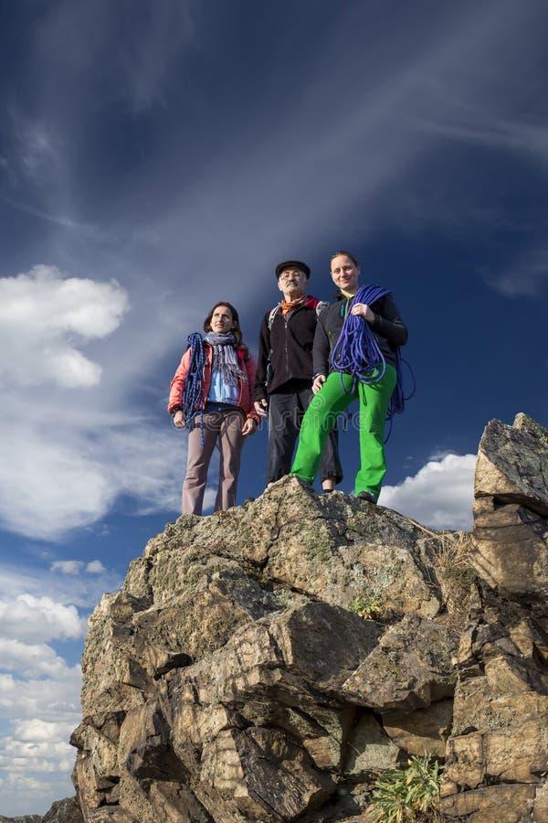 O grupo de montanhistas fica no penhasco aguçado imagem de stock royalty free