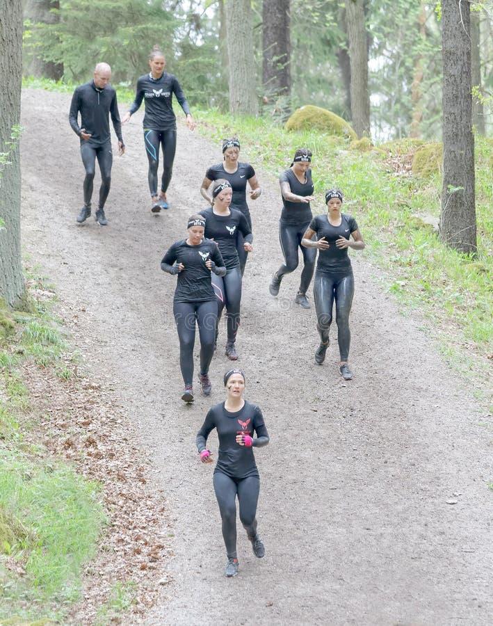 O grupo de mulher no treinamento preto veste o corredor abaixo de uma inclinação fotografia de stock royalty free