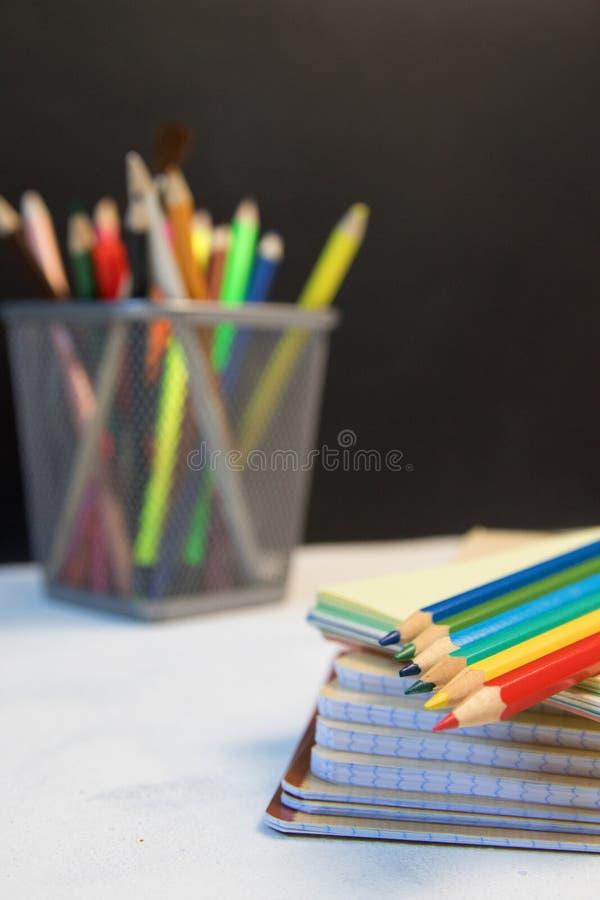 O grupo de objetos fecha-se acima do conceito de volta ao fundo do quadro-negro do preto do caderno do lápis da cor da escola atr foto de stock