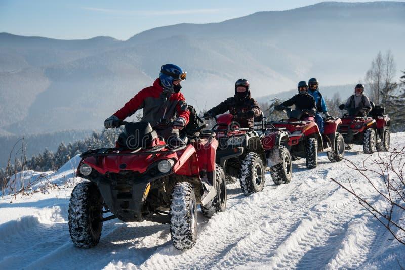 O grupo de pessoas que conduz o quadrilátero fora de estrada bikes na neve no inverno imagens de stock