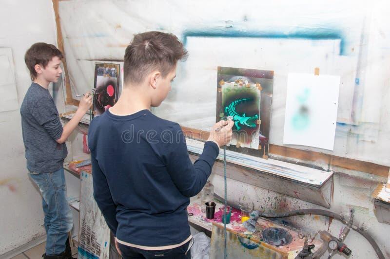 O grupo de pintura dos adolescentes das crianças com um aerógrafo coloriu brilhantemente imagens em um estúdio artístico - Rússia imagem de stock